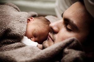 Dad cuddling newborn baby