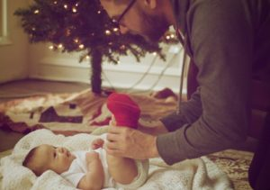 Father playing with baby under christmas tree